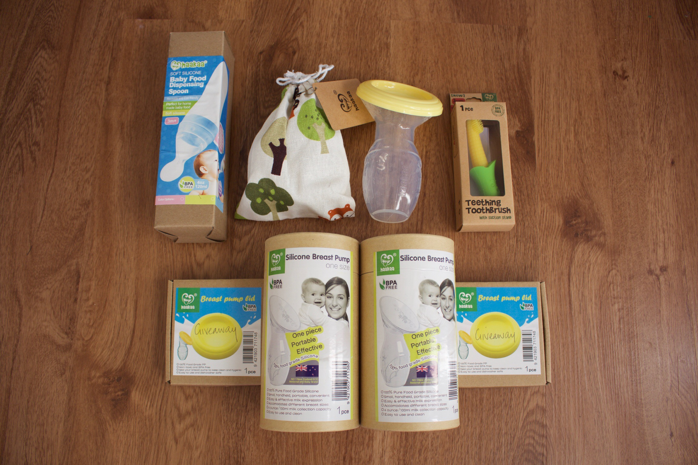 Haakaa Breast Pump review - a selection of products from Haakaa including the Haakaa breast pump, a teething toothbrush, a baby food dispensing spoon and the Haakaa breastpump lid