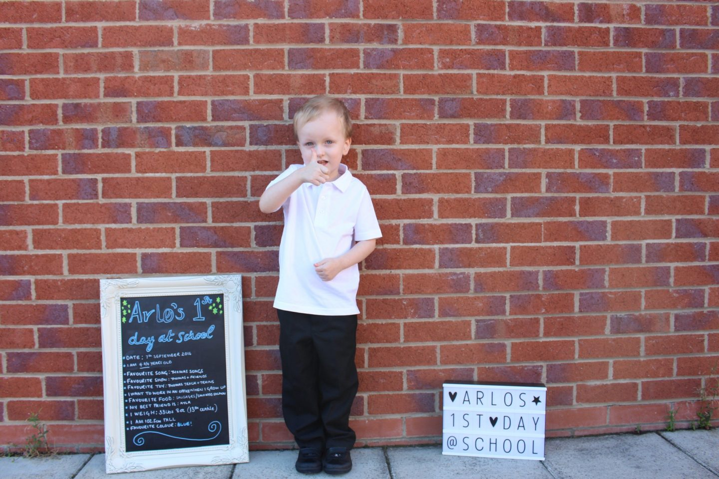 A little boy on his first day of school next to a sign that says 'Arlo's first day of school'