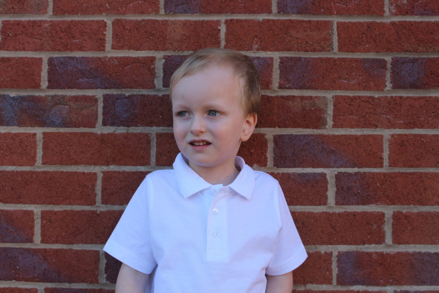 A 4 year old boy in his school top looking pensive