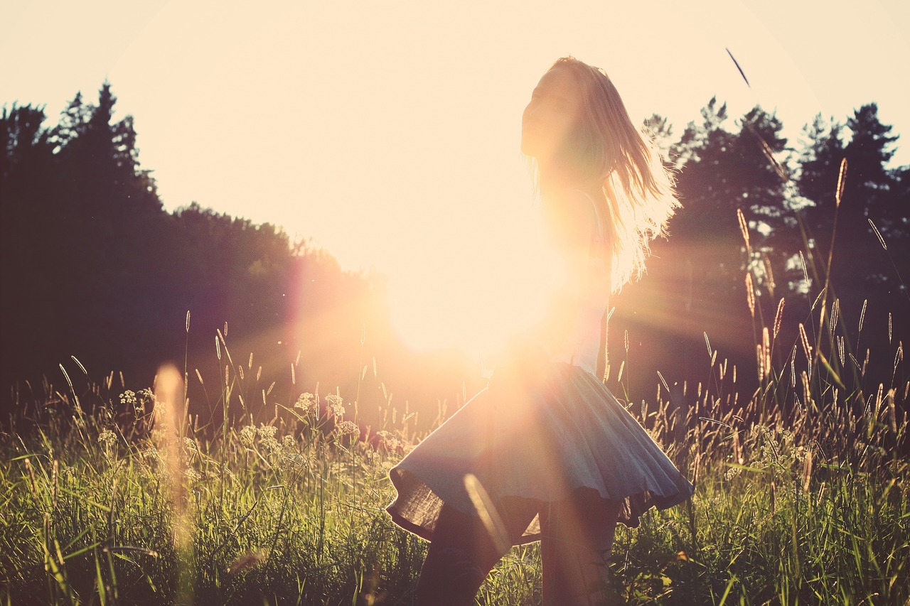 A girl twirls in a skirt in a field as the sun sets behind her