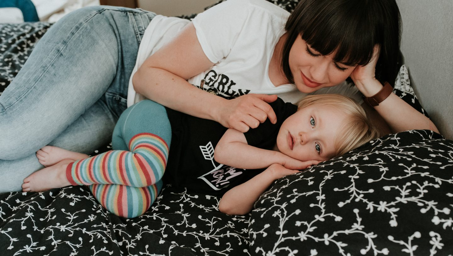 The ultimate guide to surviving when your kids don't sleep through the night - Nyomi and her daughter lay on the bed, Lena looking at the camera