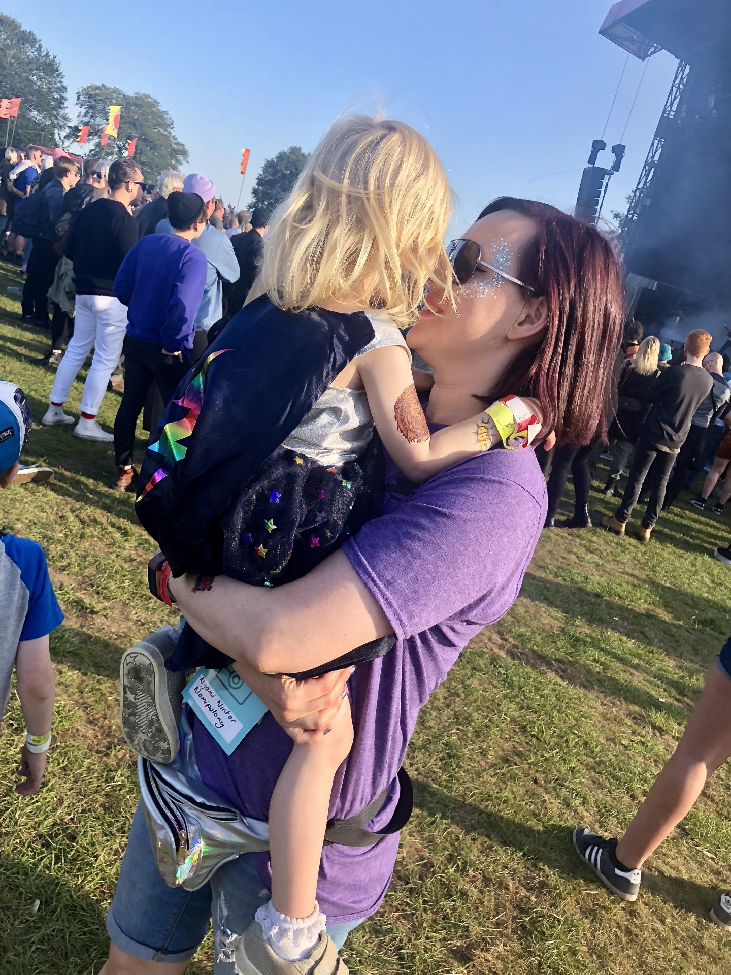 Woman carrying a 3 year old at the main stage of a festival.