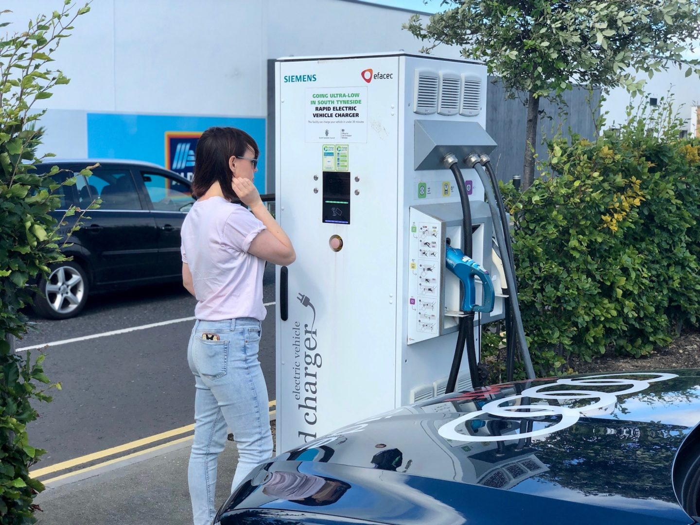 A woman looking at an electric vehicle charging point