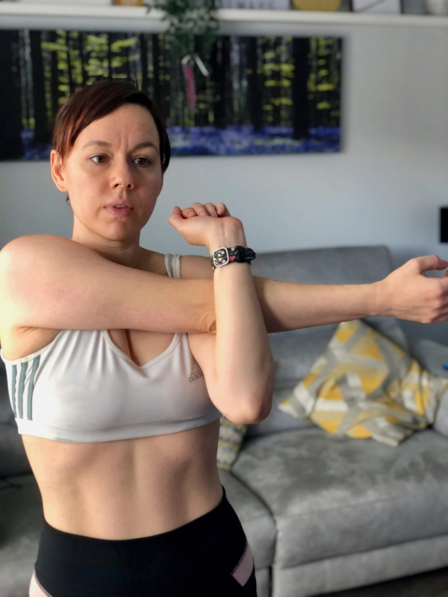 A woman wearing a sports bra stretches out her arm
