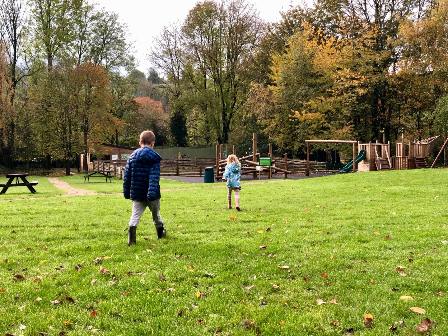 AD: Landal Sandybrook Peak District family review - a relaxing autumnal long weekend break. Kids running towards the playground at Landal Sandybrook.