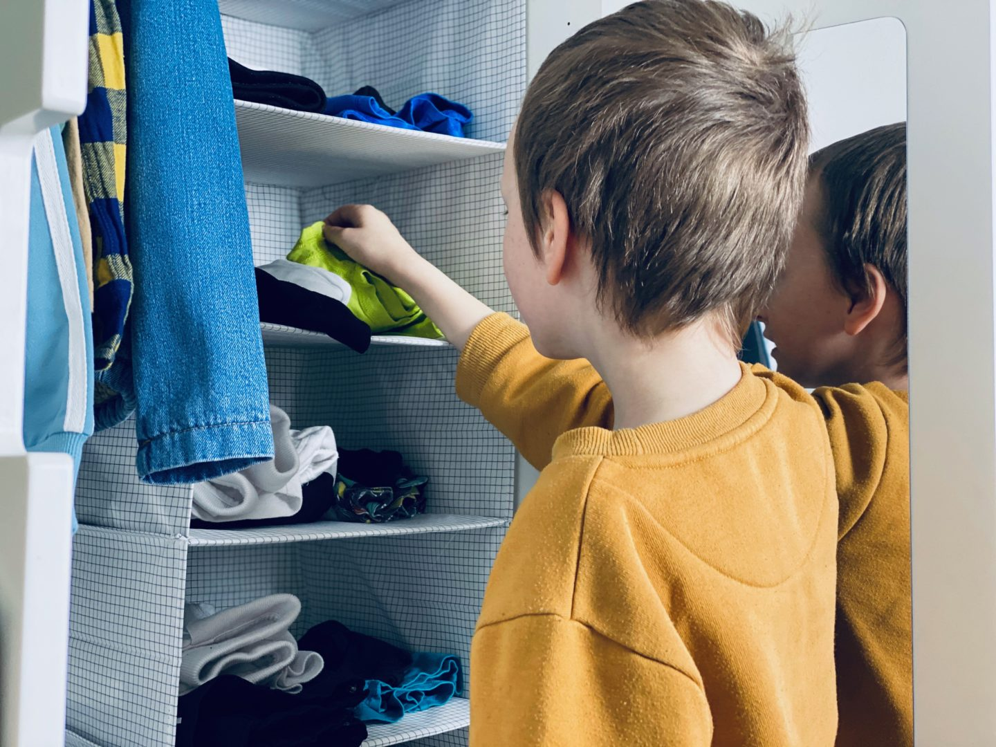 AD: Taking back control of mornings for only £51.75 with IKEA organisation hacks. 8 year old using hanging organiser to get dressed.