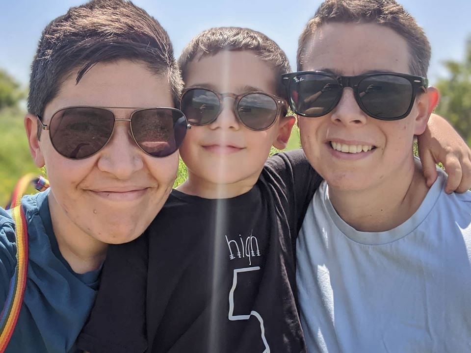 Two women wearing sunglasses hugging a boy. All are smiling.