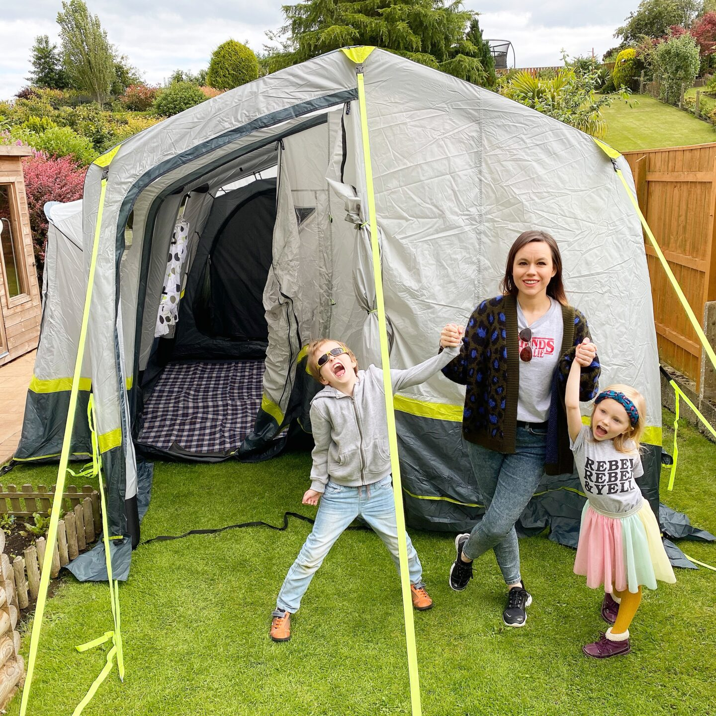 A mother and her son and daughter stand in from of ab OLPRO Home 5 birth family air tent looking happy and excited.