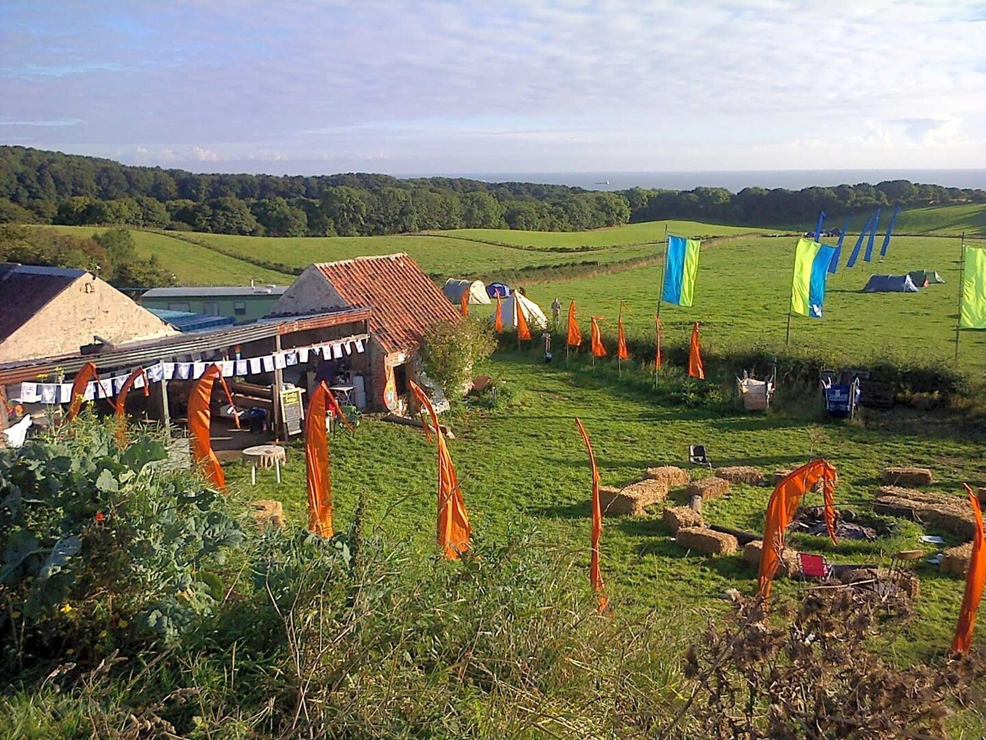 A farm and campsite with colourful flags overlooking the sea.