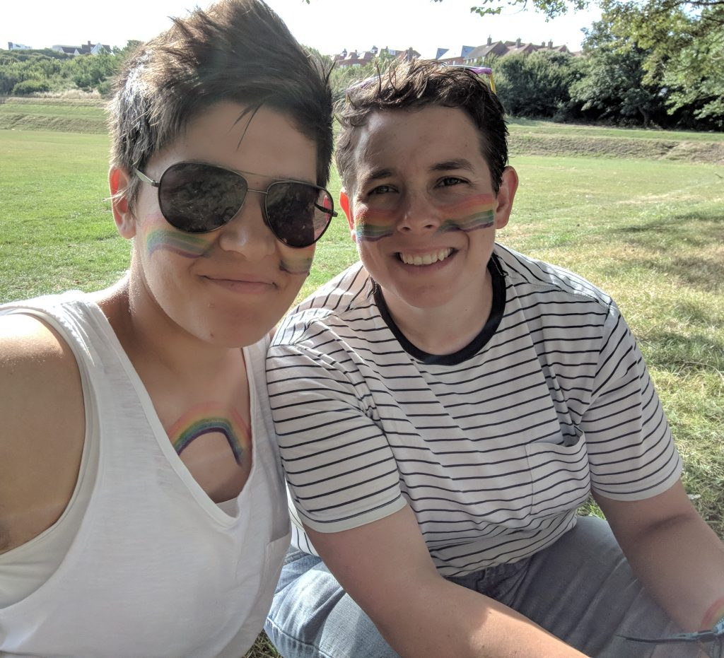 Two woman sat together in a field. Both have rainbow facepaint on and both are smiling.