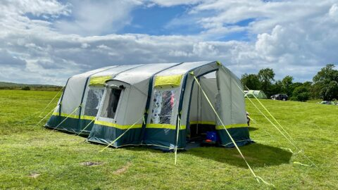 The OLPRO Home 5 berth family tent which is large, light grey, blue and neon green accents in a field.