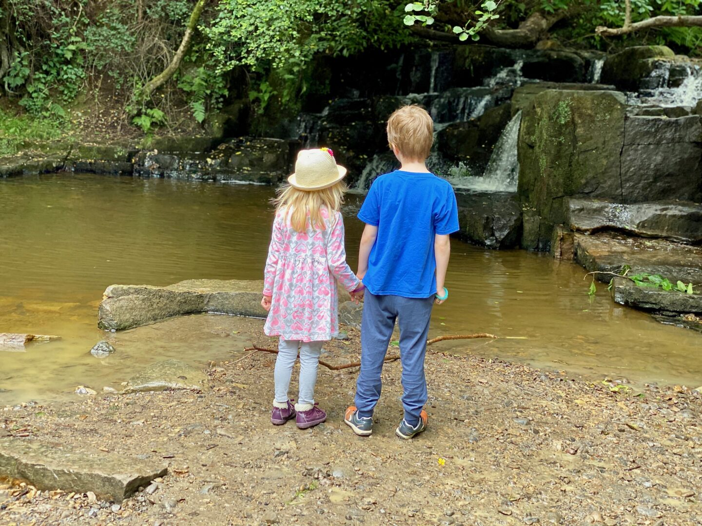 Two children holding hands looking at small waterfalls