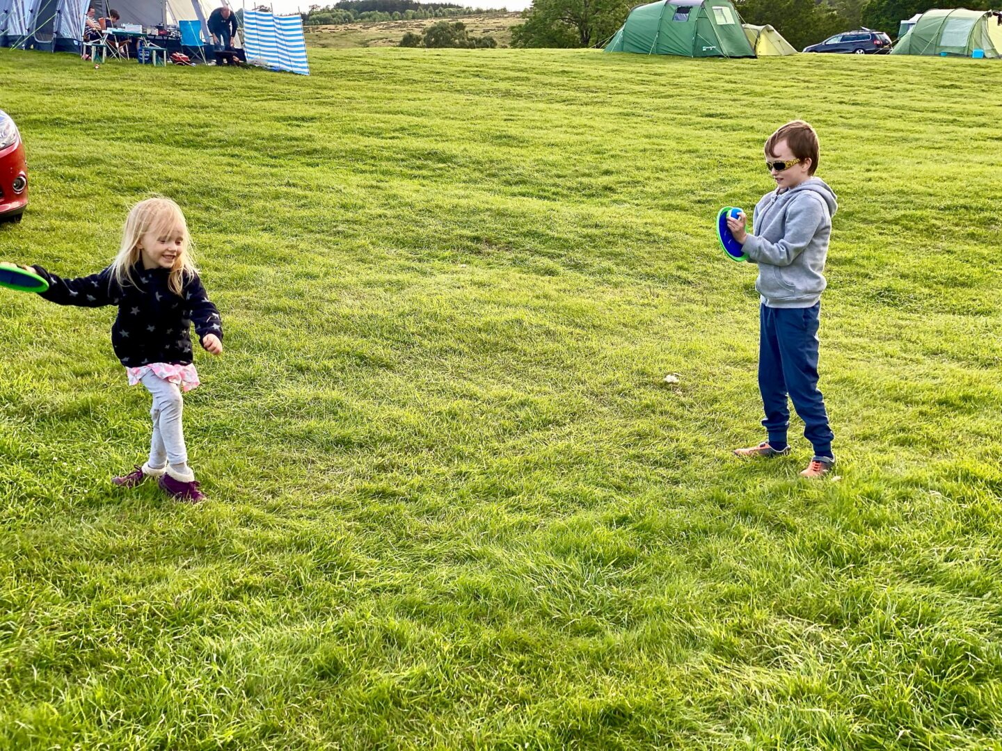 two children playing catch on a campsite