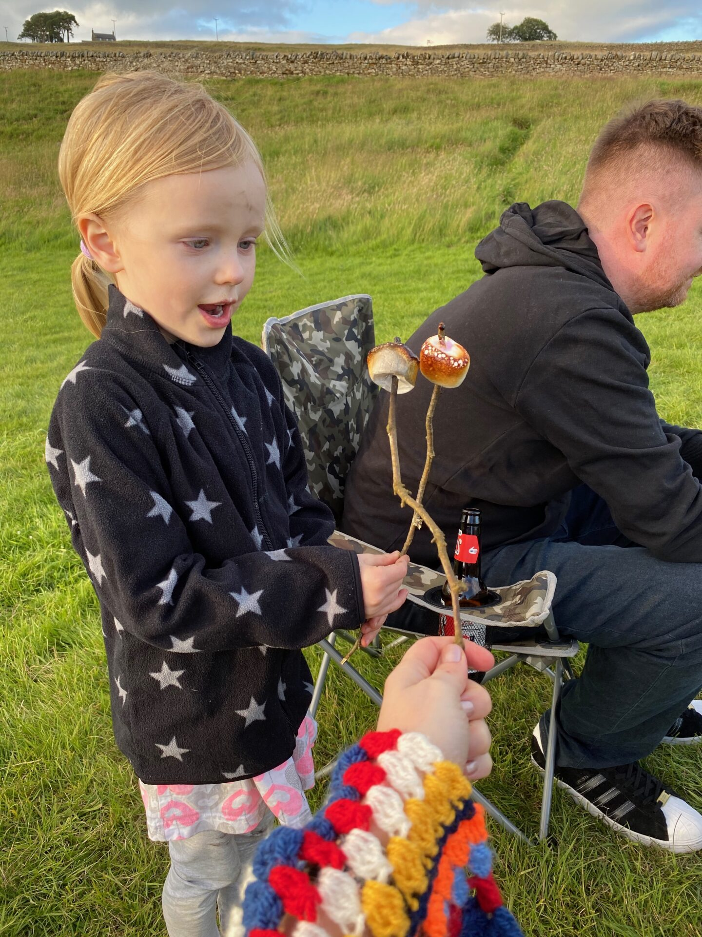 Little girl with blonde hair holding sticks with toasted marshmallows