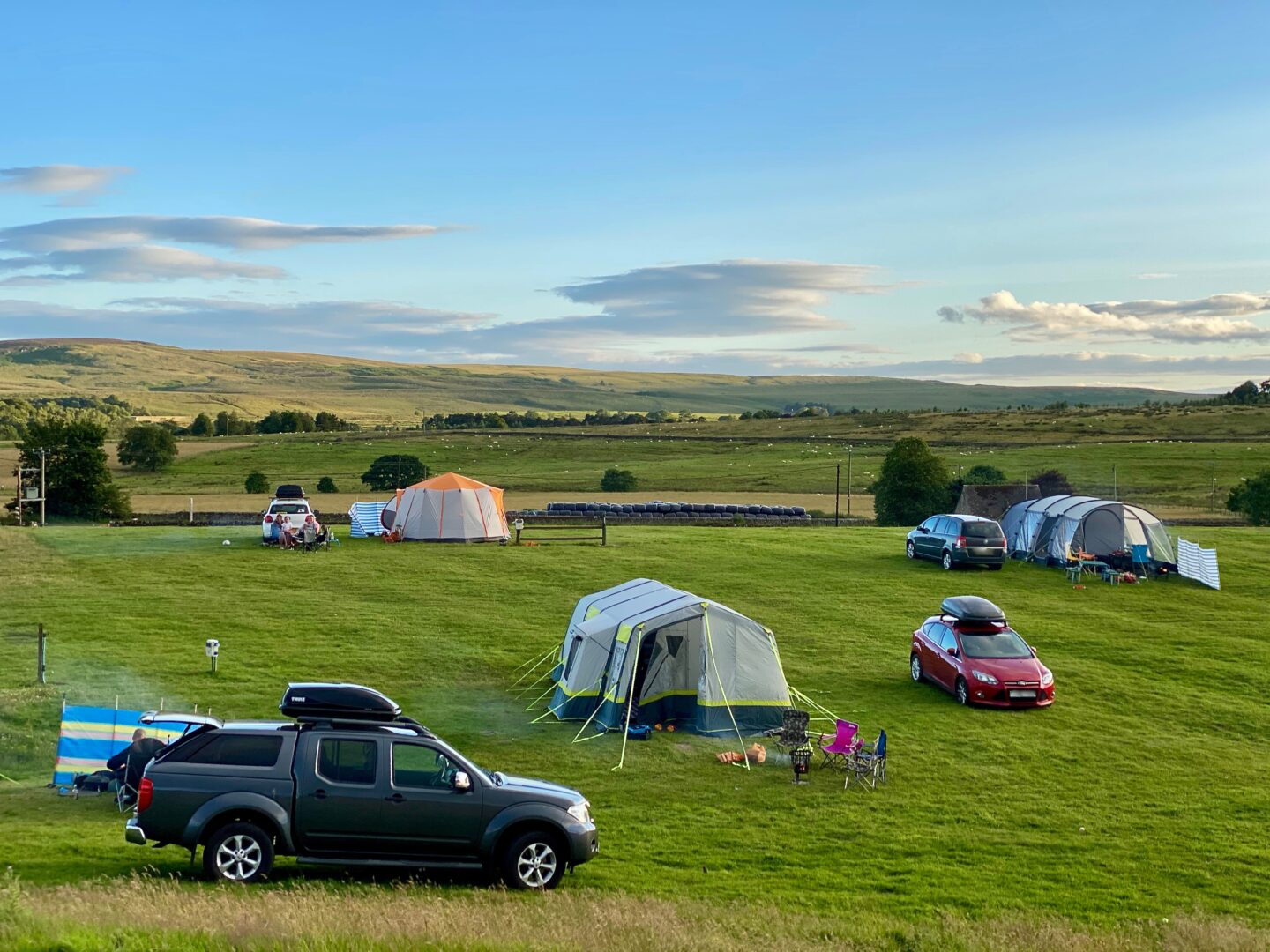 A campsite with 3 cars and tents