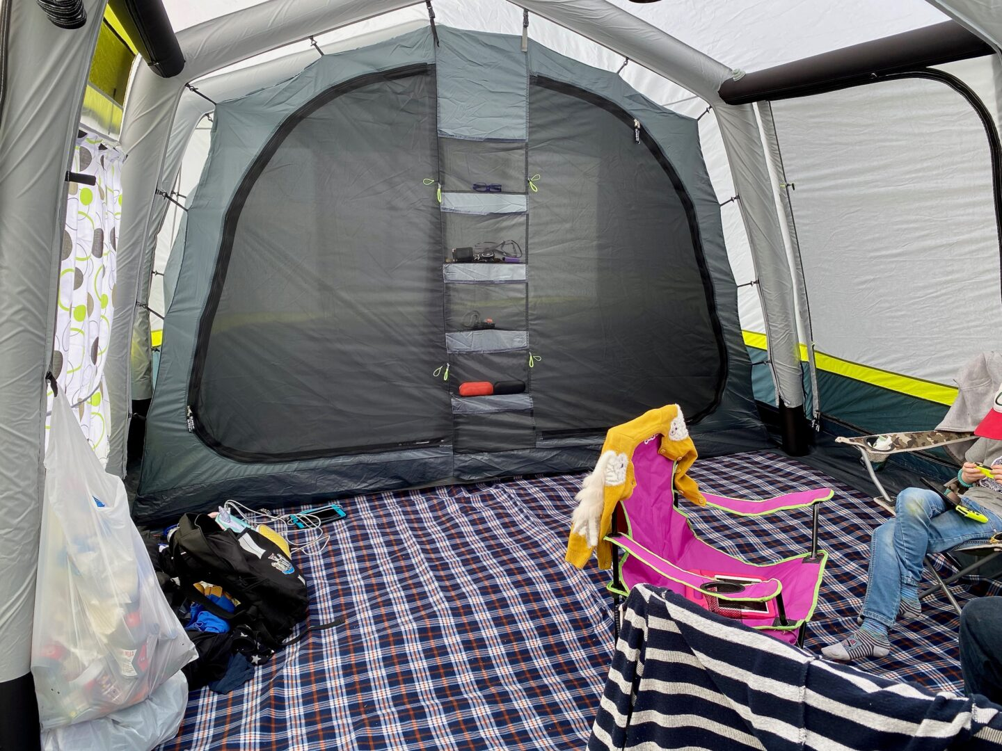 The inside of a tent with storage pockets and a tent carpet