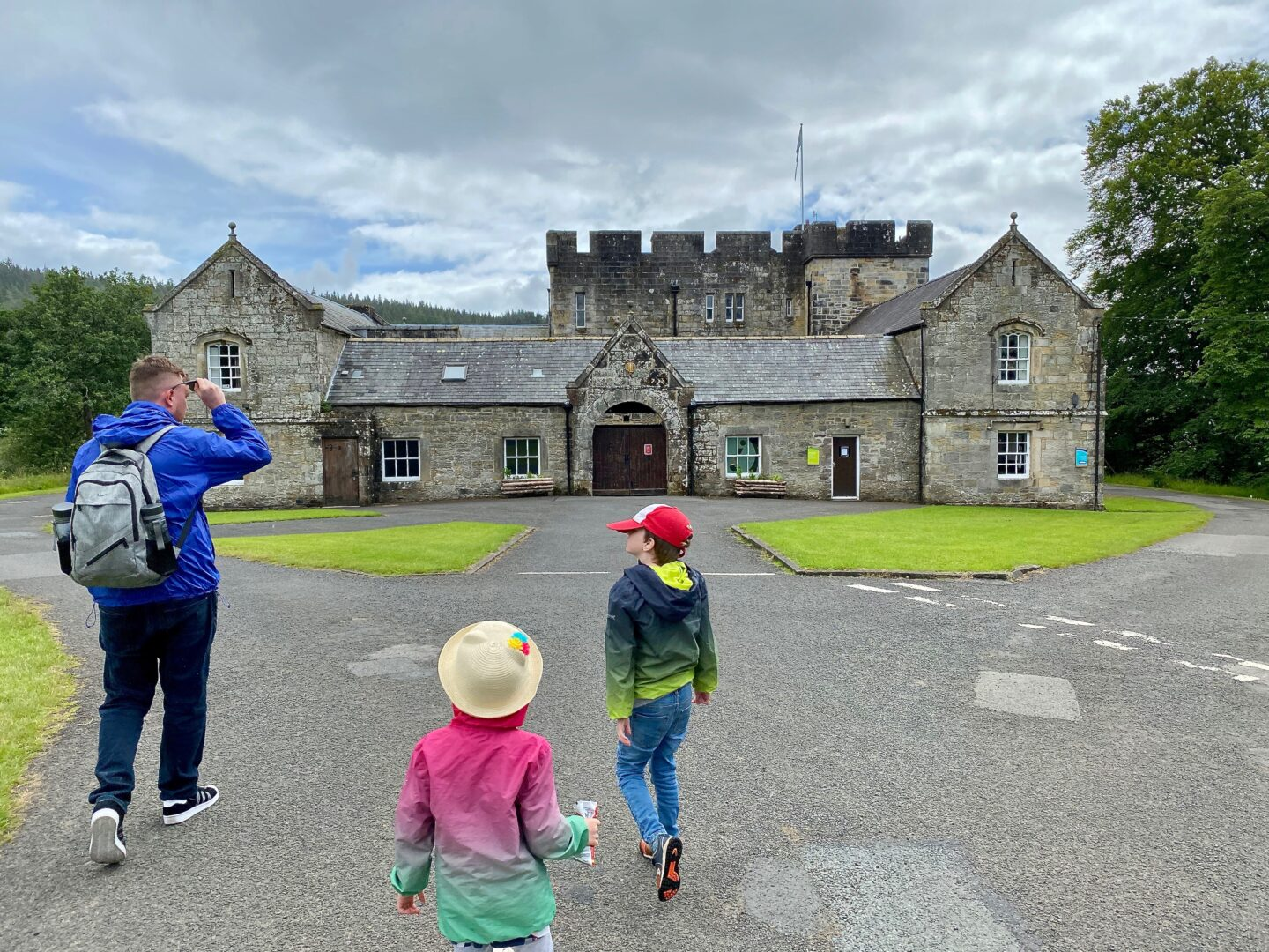 A picture of Kielder castle with a man and 2 children
