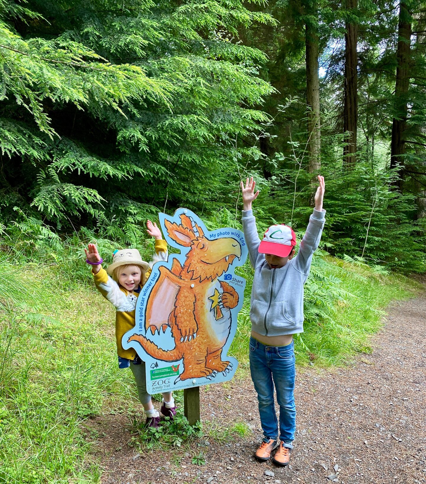 2 children holding their arms up in the air next to a Zog sign that makrs the end of a trail