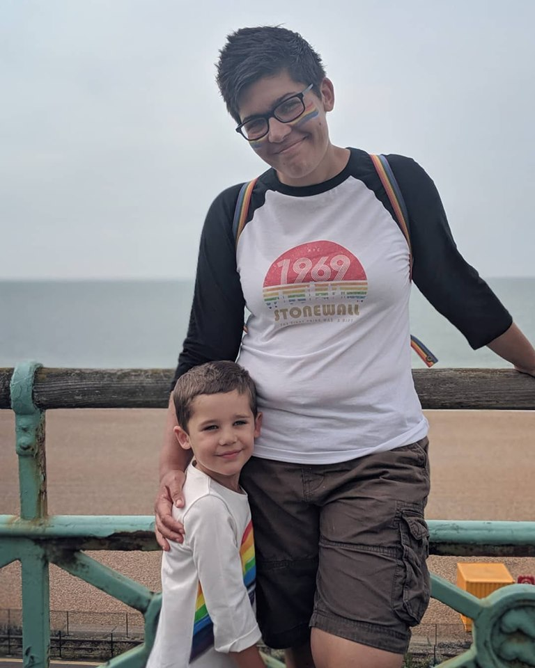 Woman with rainbow facepaint and a 1969 Stonewall t shirt hugging a boy stood at the beach.