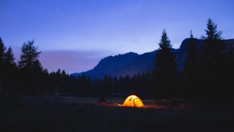 Tent glowing against the mountains during wild camping at night.