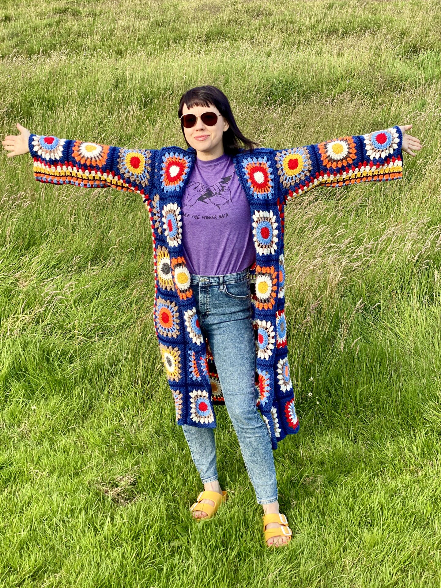 A brunette woman wearing sunglasses and a colourful 70s style crochet Rebecca Cardigan stood in a field with her arms spread wide.