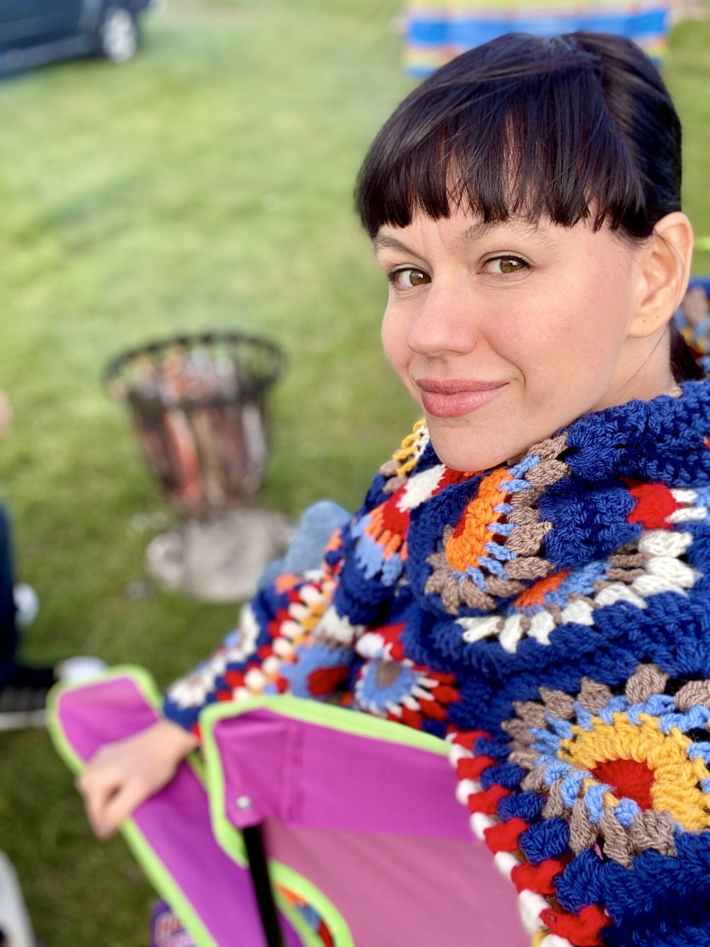 Brunette woman sat in front of a camp fire wearing a colourful crochet Rebecca Cardigan from This Is Us.