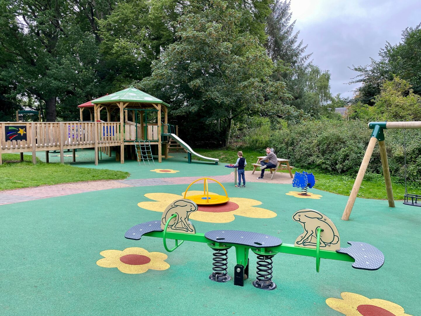 A play park showing a slide, climbing apparatus and a see saw