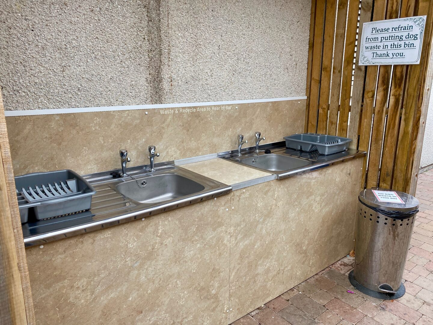 The dishwashing facility of two sinks with two drainers and a bin.
