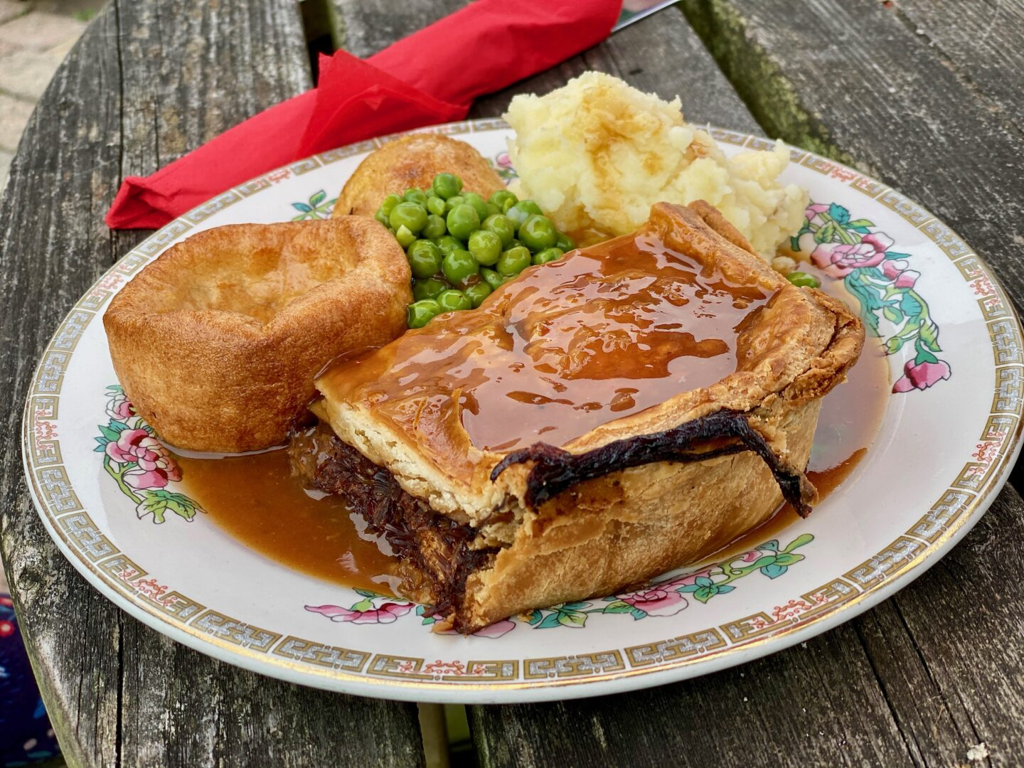 Pie, mash, peas, yorkshire pudding and gravy on a plate