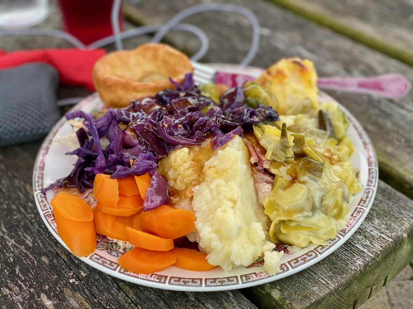 A plate filled high from a carvery with carrots, mash, red cabbage, creamed leeks, gammon, cauliflower cheese and a yorkshire pudding.