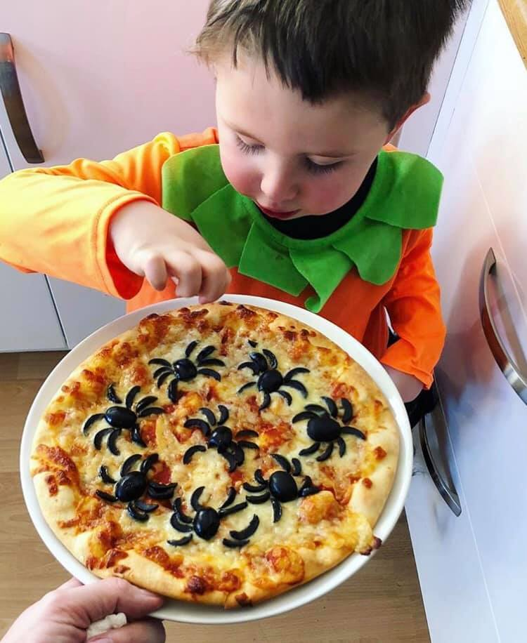 Boy with a pizza with spiders made from olives