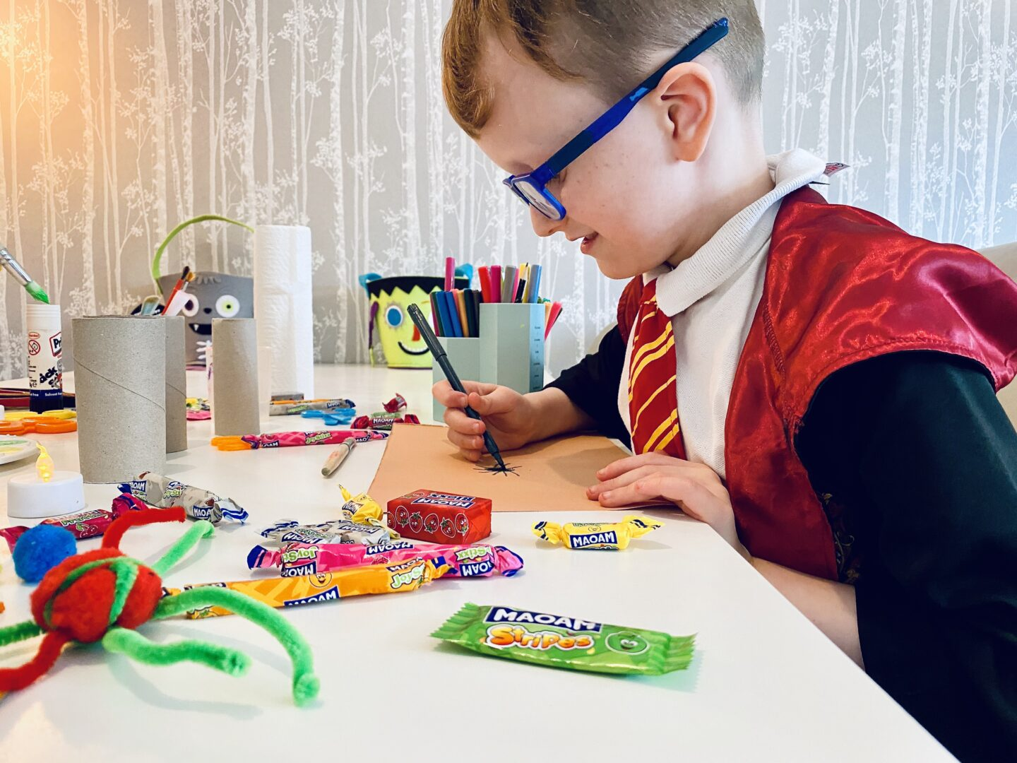 A boy dressed as Harry Potter doing Halloween crafts