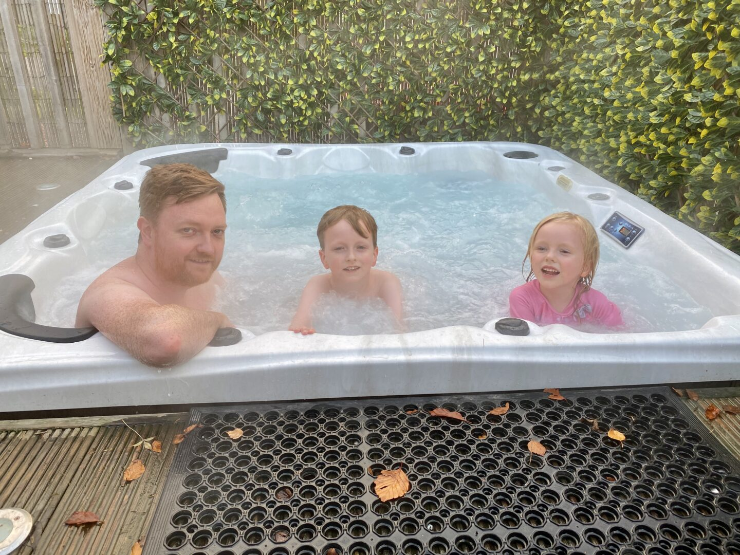 Father, boy and girl in a hot tub