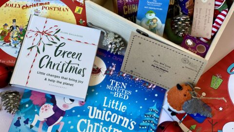 A box full of Christmas items like hot chocolate, books and an elf
