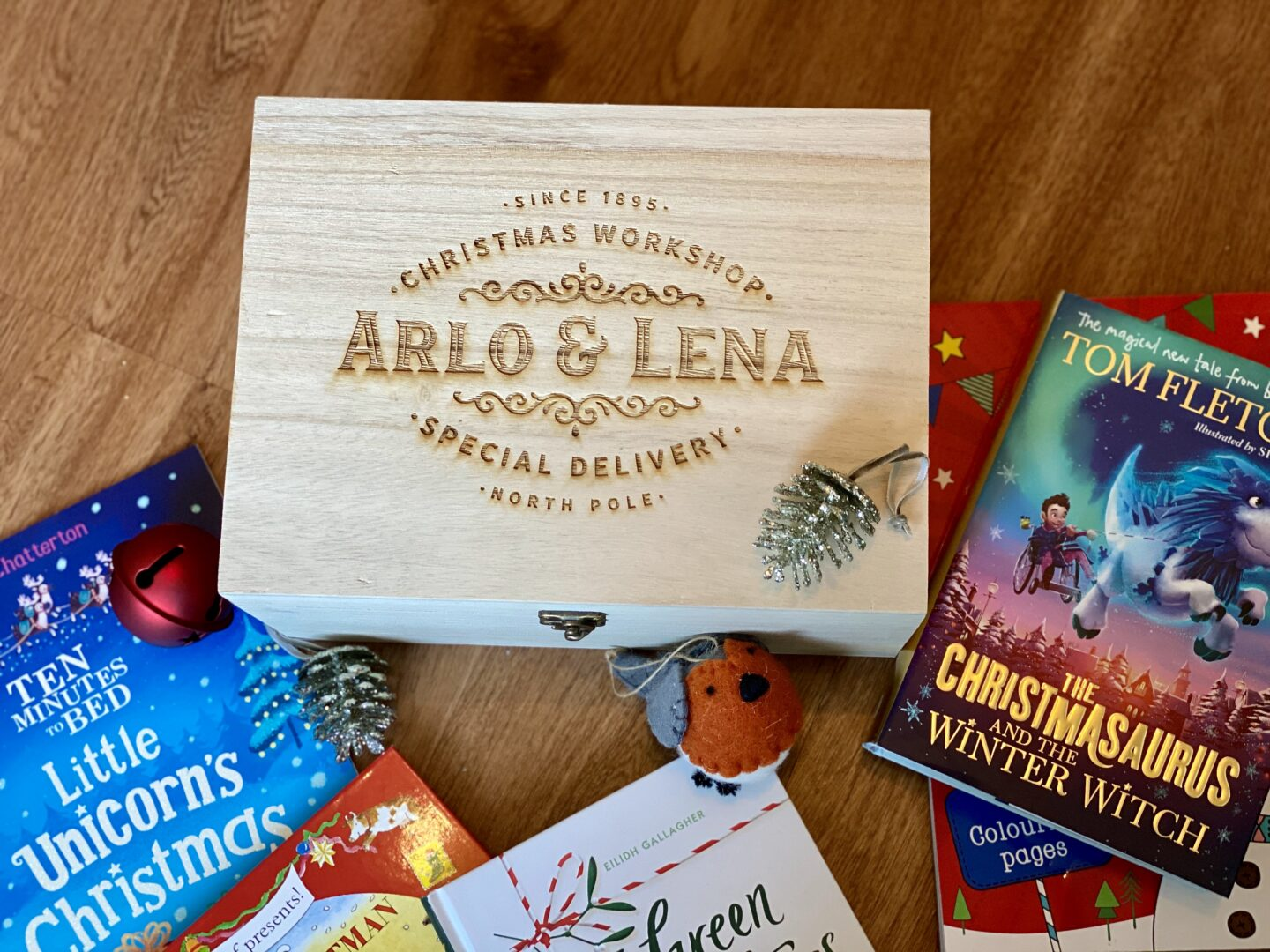 An engraved wooden Christmas tree day box that has the names to Arlo and Lena engraved in it. Surrounded by christmas books