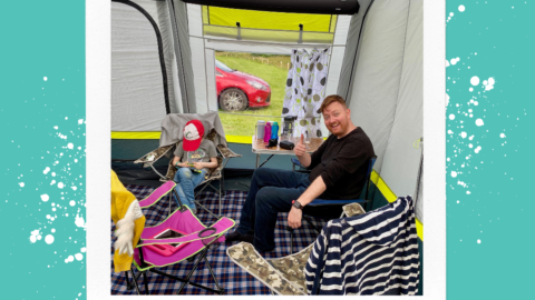 A father and son sat on camping chairsinside of a tent