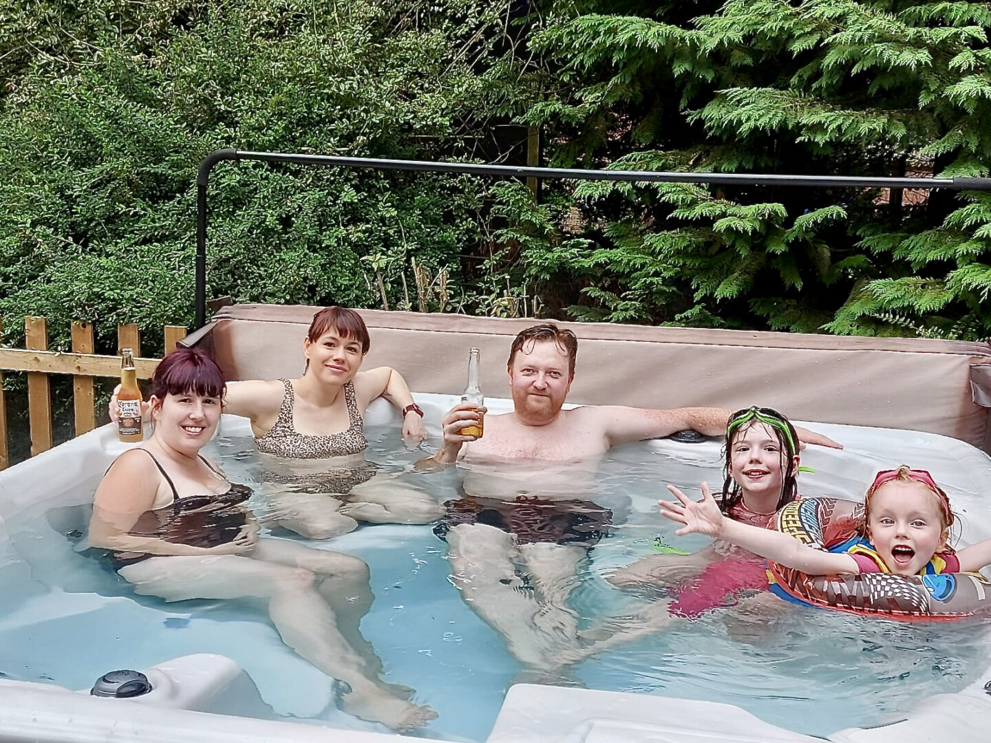 2 women, a man and 2 girls in a hot tub smiling and having fun.