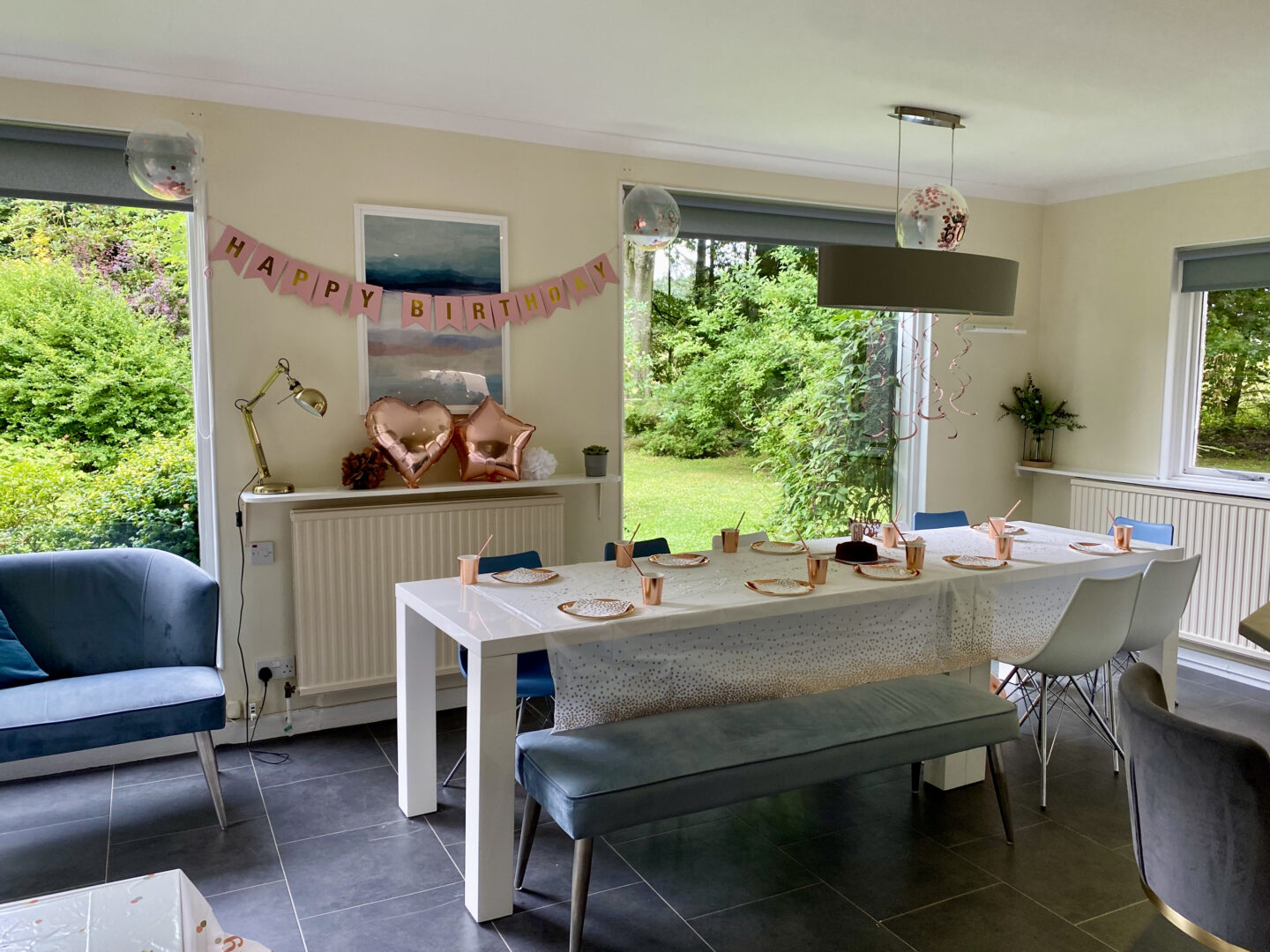 A large kitchen with a white table decorate for a birthday with rose gold decorations