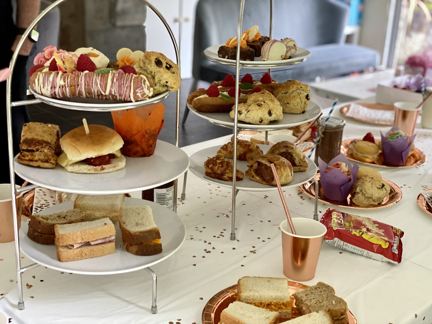 An afternoon tea set out on a dining table on cake stands