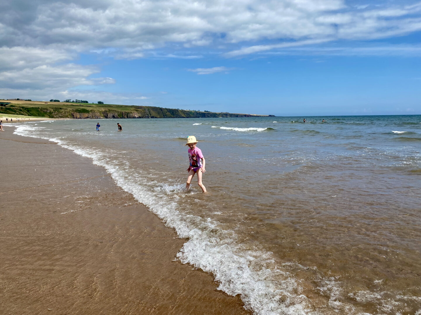 A little girl plays in the waves at Lunan Bay, Angus, Scotland