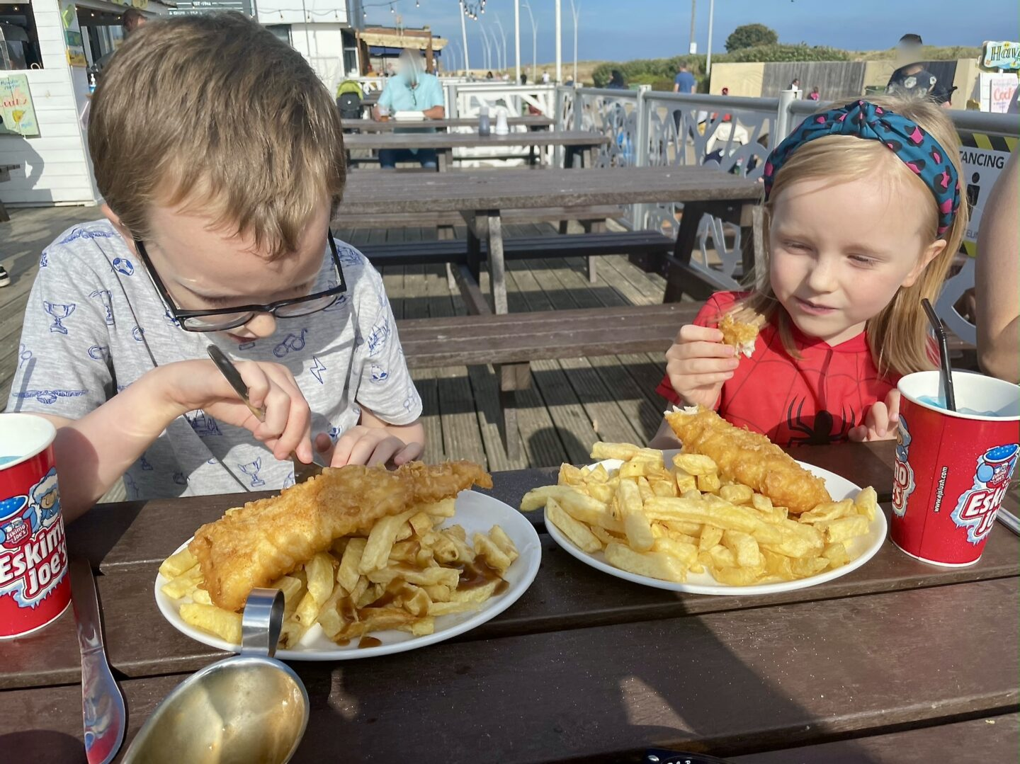 A boy and girl eat plates of fish and chips