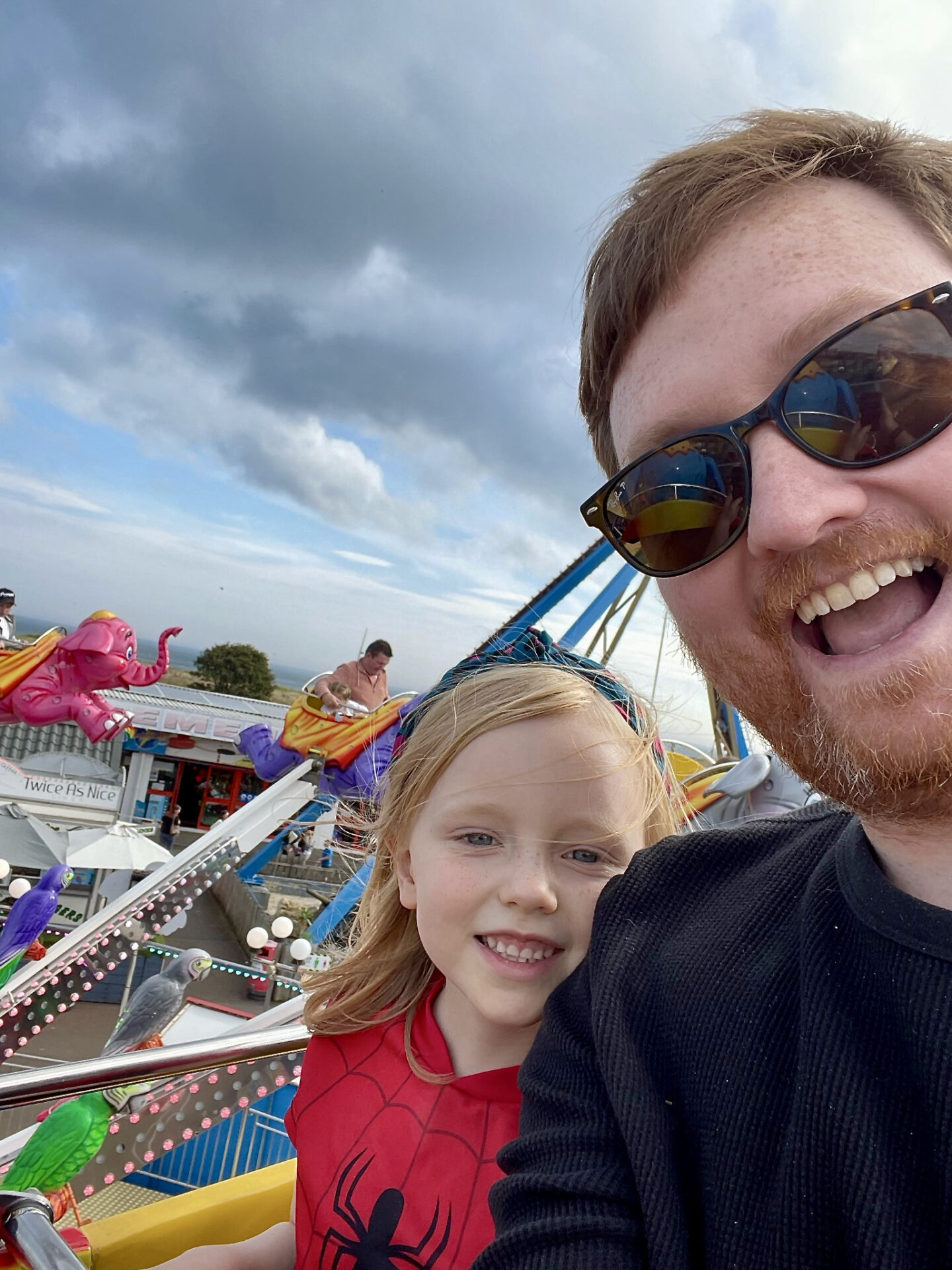 A father and daughter smiling on a fairground ride