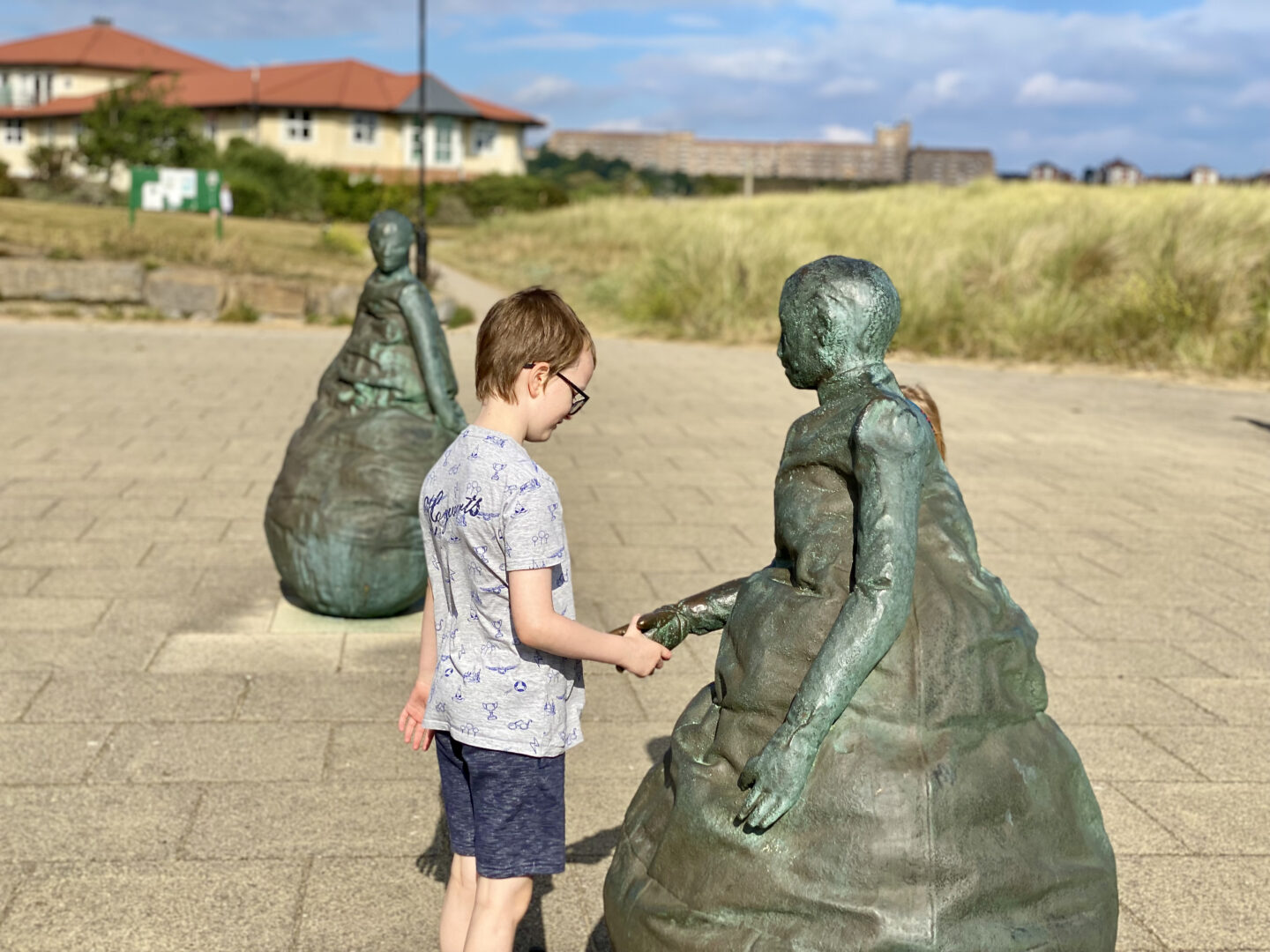 A boy 'shakes hands' with a statue