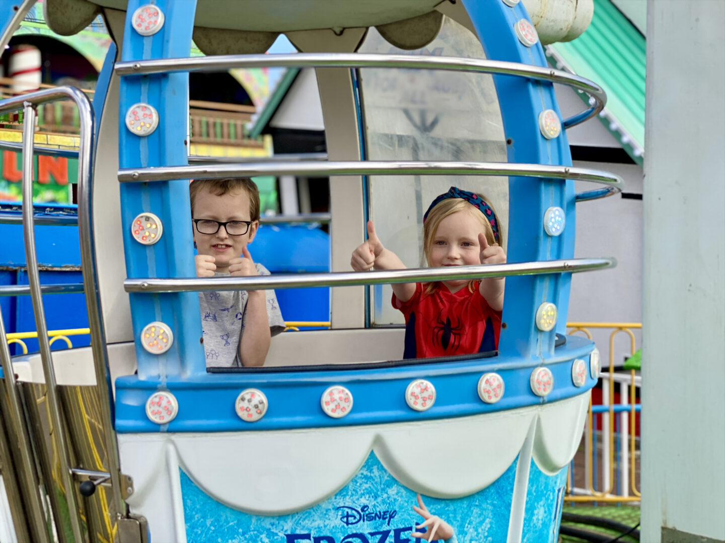 a boy and girl smiling on a ferris wheel ride