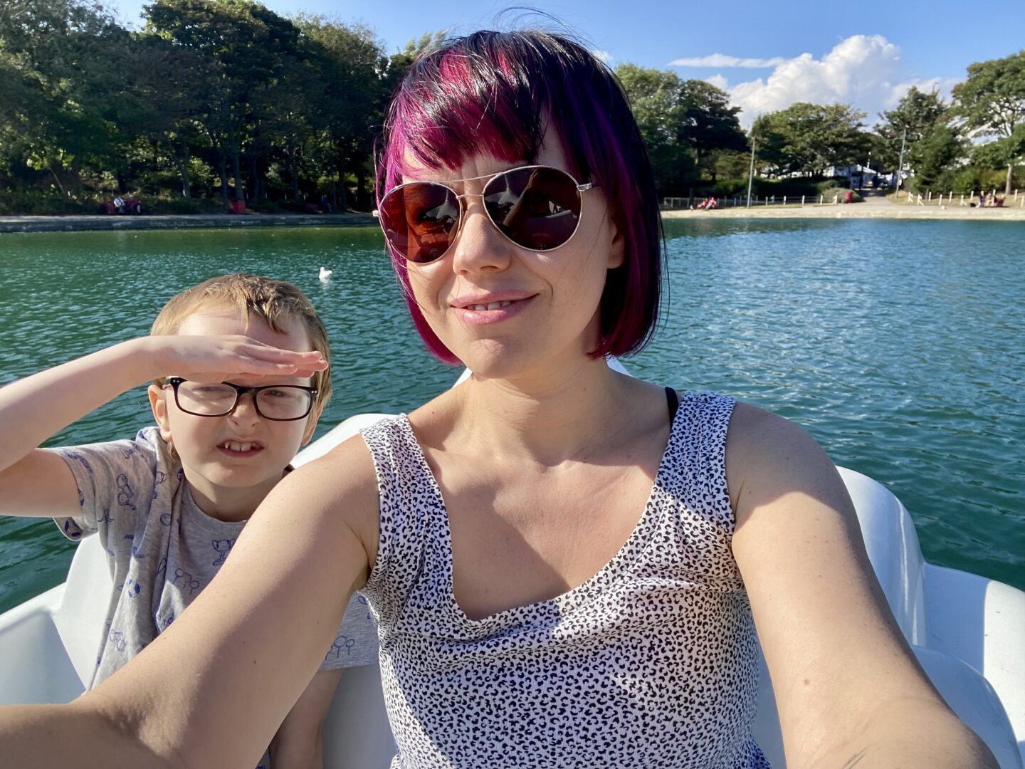 a woman and 9 year old boy on a boat in a boating lake