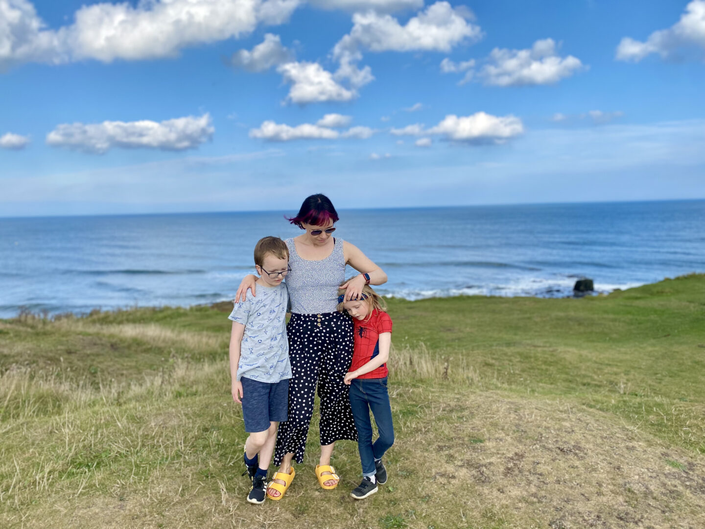 A mam cuddles her son and daughter standing on a cliff top overlooking the sea