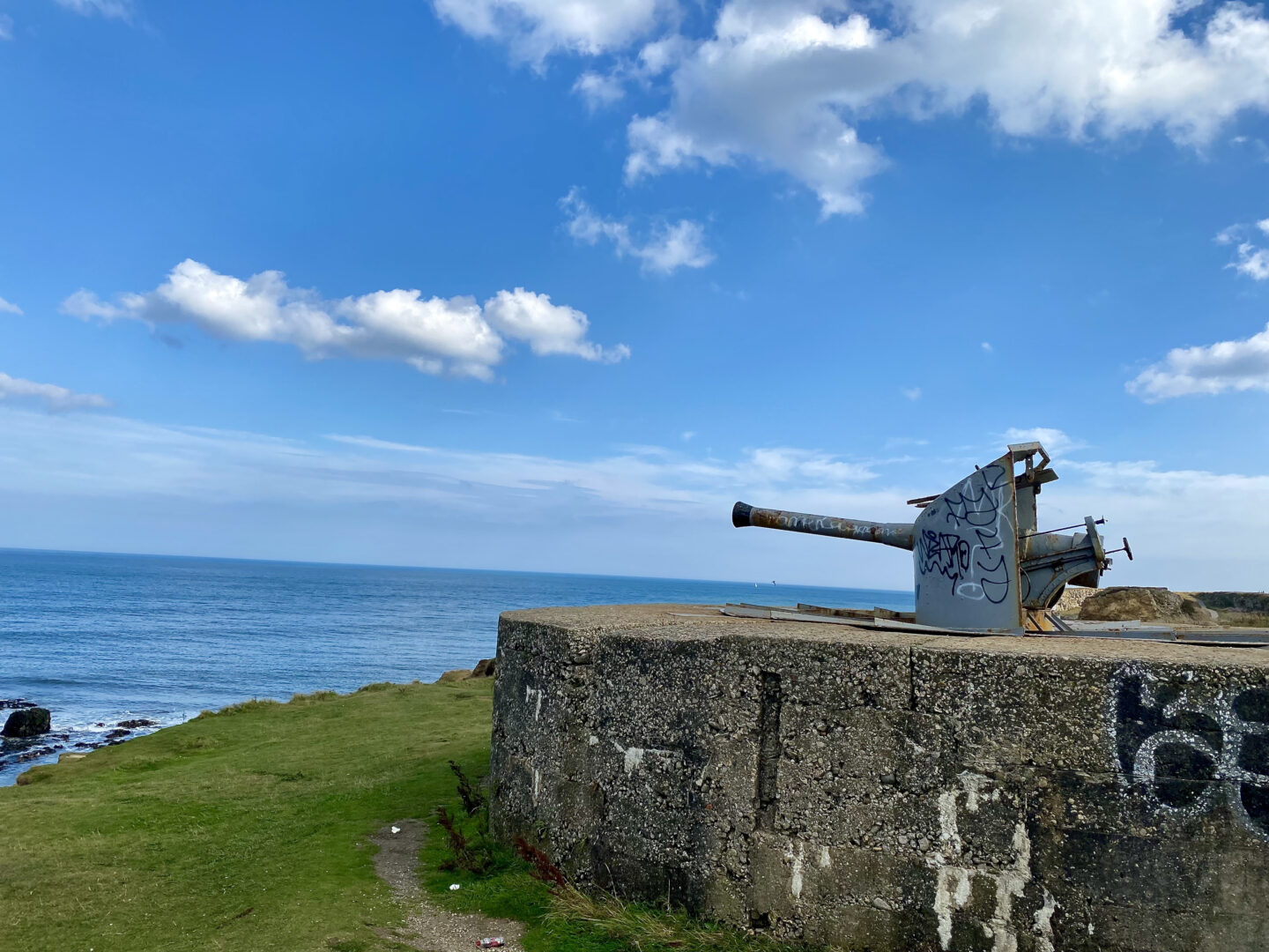 A large grade 2 listed military gun stands on a cliff top