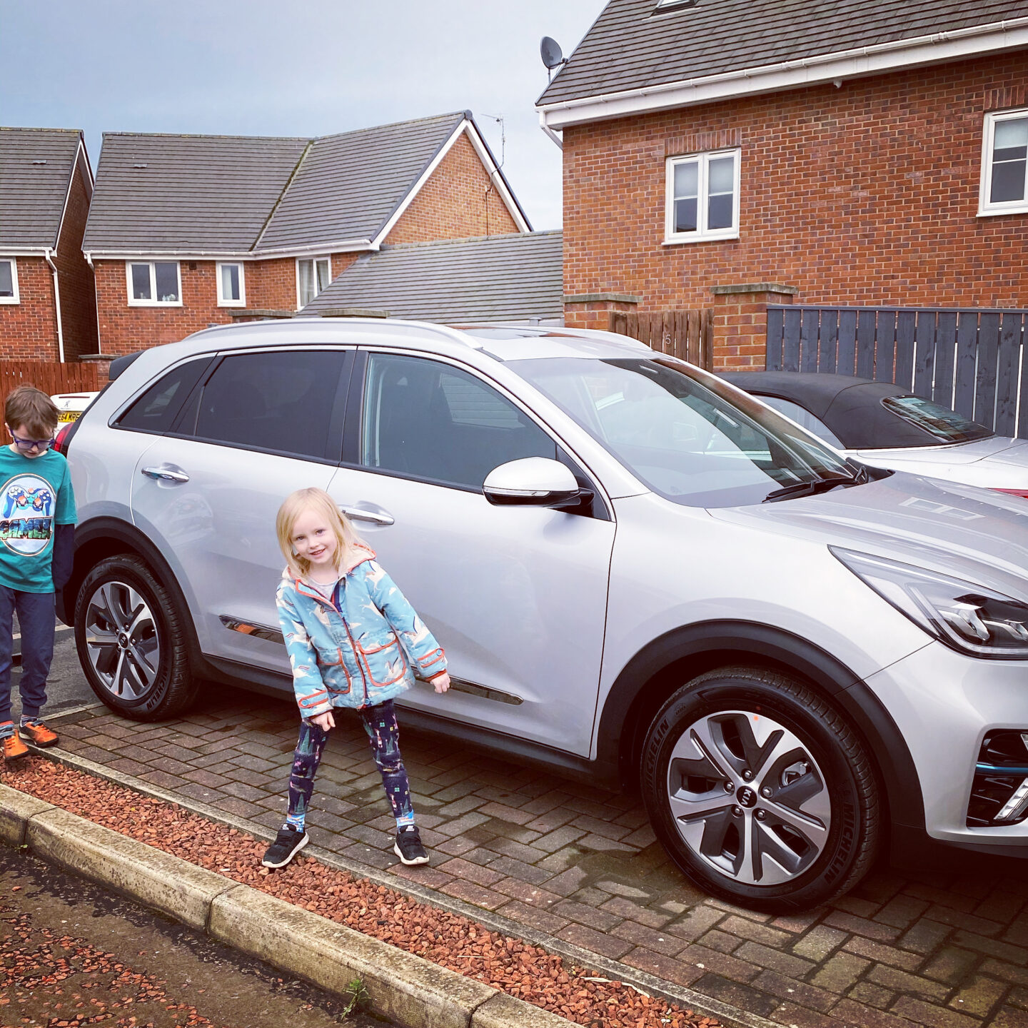 Children look happy around their new silver electric car