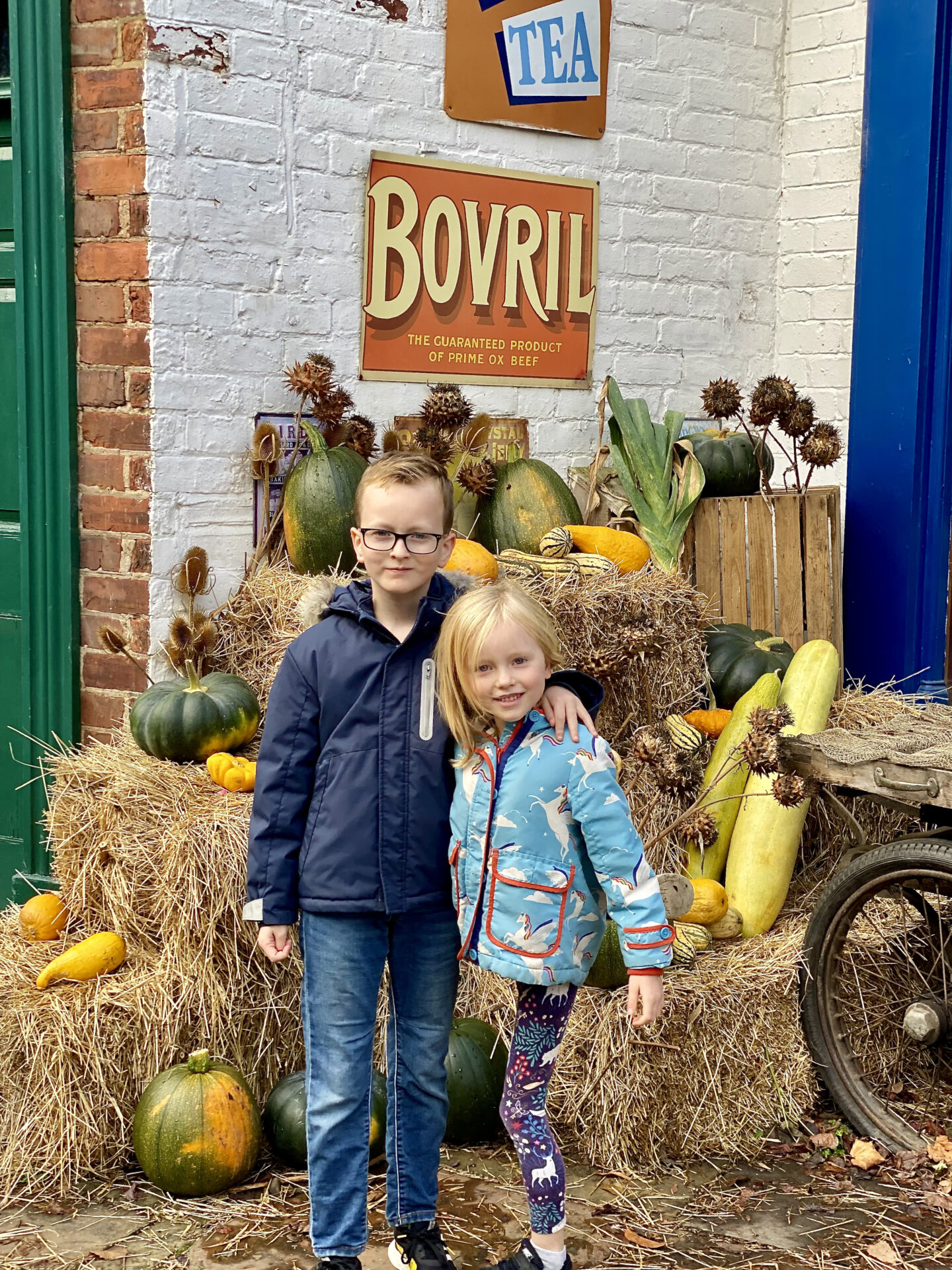 2 children smile in front of a display of pumpkins at Preston Park museum