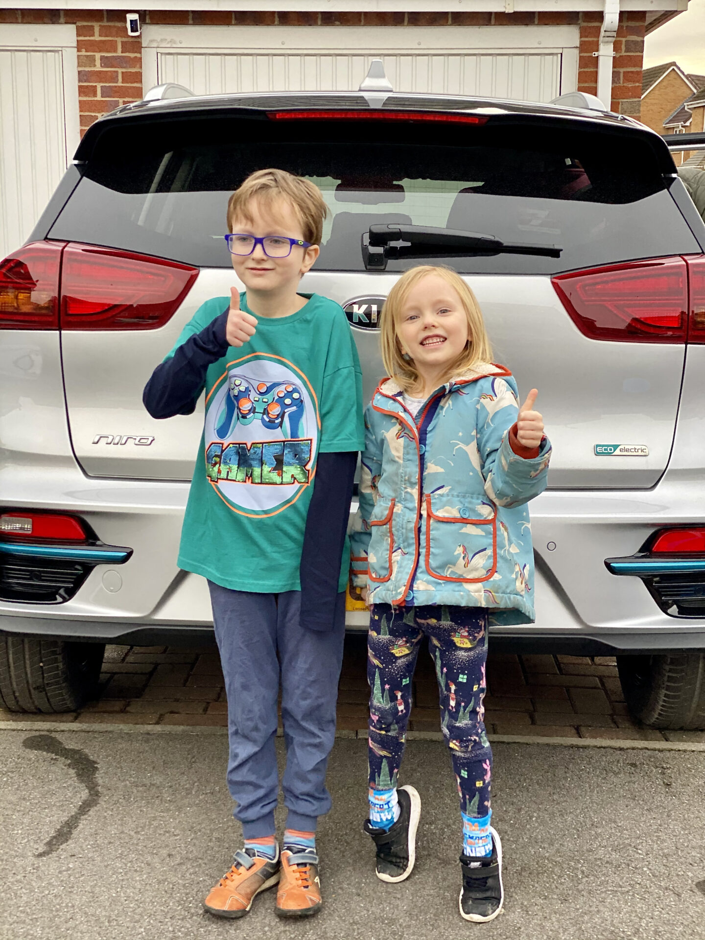 2 children smile with their thumbs up in front of a silver electric car